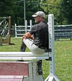 Peter watches his team train at his grass Grand Prix ring.